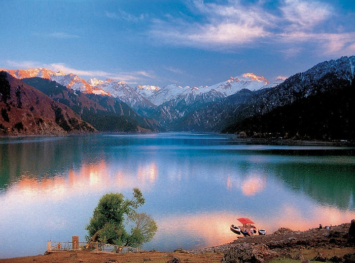 阜康市境内。是以高山湖泊为中心的自然风景区。天山博格达峰海拨5445米,终年积雪,冰川延绵。天池在天山北坡三工河上游,湖面海拨1900多米。湖畔森林茂密,绿草如茵。随着海拨高度不同可分为冰川积雪带、高山亚高山带、山地针叶林带,和低山带四个自然录象带。在天池同时可观赏雪山、森林、碧水、草坪、繁花的景色。附近还有小天池、灯杆山、石峡等景点。天池石古称瑶池,清乾隆时始以天镜、神池之意命名为天池。 新疆天山天池是古冰川运动创作的冰碛湖,在地球上第四纪以来的冰川运动共有四次,天池的形成大致可划分为三个阶段